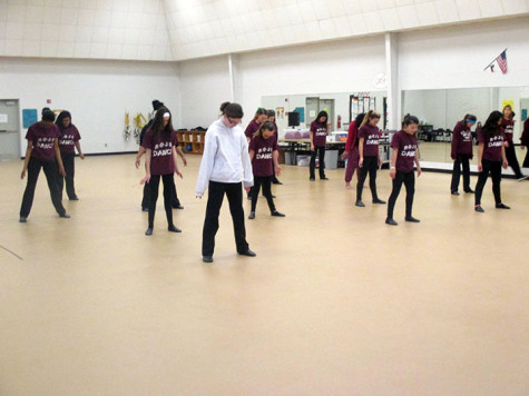 The dancers stand in formation as they practice their moves.