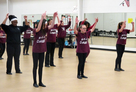 Cathy Isaacs' dance class stops and puts their hands up as part of their dance routine.