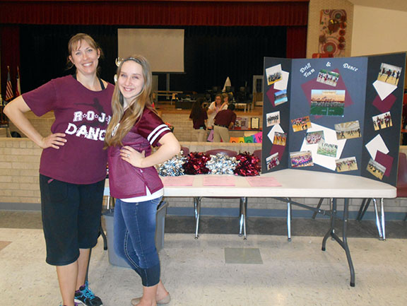 Dance teacher Catharine Isaacks and drill team member Emma Ness stand by their table on March 24, 2015 at the elective fair for incoming 7th graders.