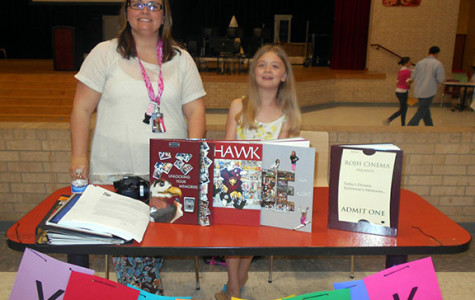 Buy your yearbook! 7th grade English and yearbook teacher Dawn Rickman displays all the yearbooks from past years. On March 24, 2015 at the elective fair for incoming 7th graders.