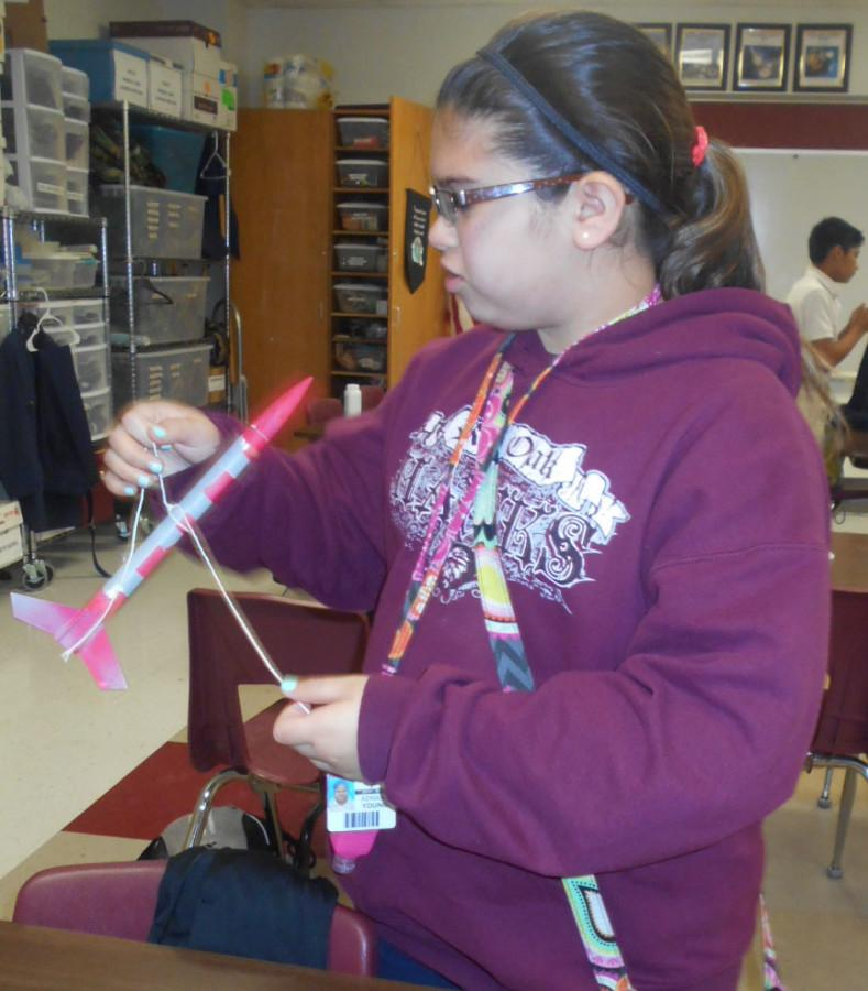 Adrianna Young ties a string around her rocket to see if it will fly steadily.