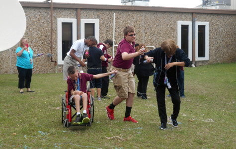 TLC teacher Kelly Blalock and her class enjoy the silly string fight with Malea Jaffe's 4th period art class in the Red Oak Junior High courtyard April 1.