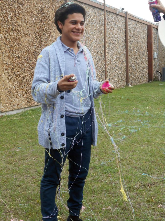 8th grade student Geovanny Velasquez stands in the ROJH courtyard while being sprayed by fellow classmates.