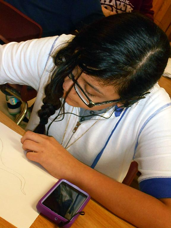 A student listens to music as she works on her art project in class. Many teachers feel listening to music can spark focus and creativity, while others think it is too distracting.