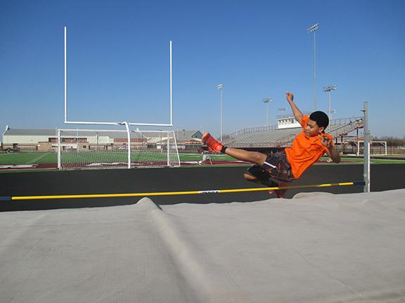 Todd Tillis practices the high jump during track and field practice.