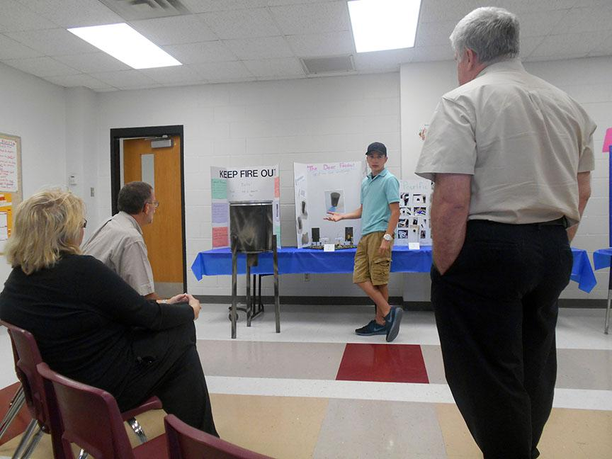 3rd place winner Nathan Morgan shows off his invention to the engineers on April 27, 2015 at the Red Oak Jr. High.