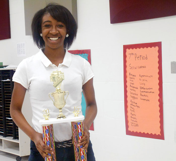 Eighth grader Cierra Andrews standing with First Division trophy.