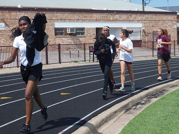 Nia Carter, Brianna Richardson, Zanobia Willis, and Sydney Sonnier are running a mile in athletics to get ready for the next track season.