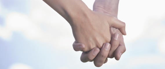 Close-up of a couple holding hands in field