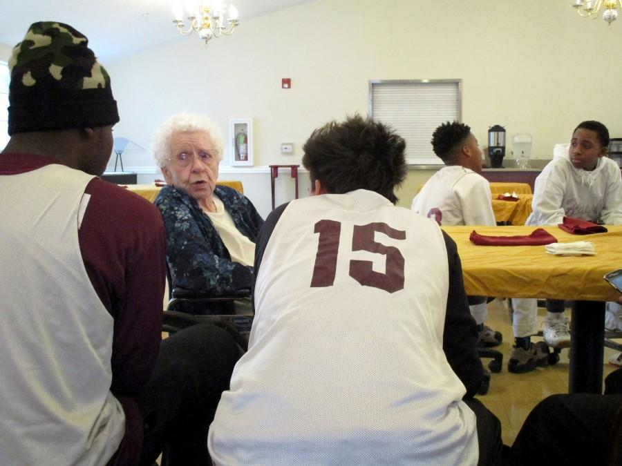 Mary Rowlette, 96-years-old, talks to Red Oak Middle School basketball players Kade Williams, left, and Benny Yuhanna, center, while Raymond Gay, second from right, and Kace Williams chat during the team's community service visit to Red Oak Health & Rehabilitation Center on Saturday, Jan. 6. The boys visit the center once a month as part of a community service project started by the team's head coach Christopher Walker.