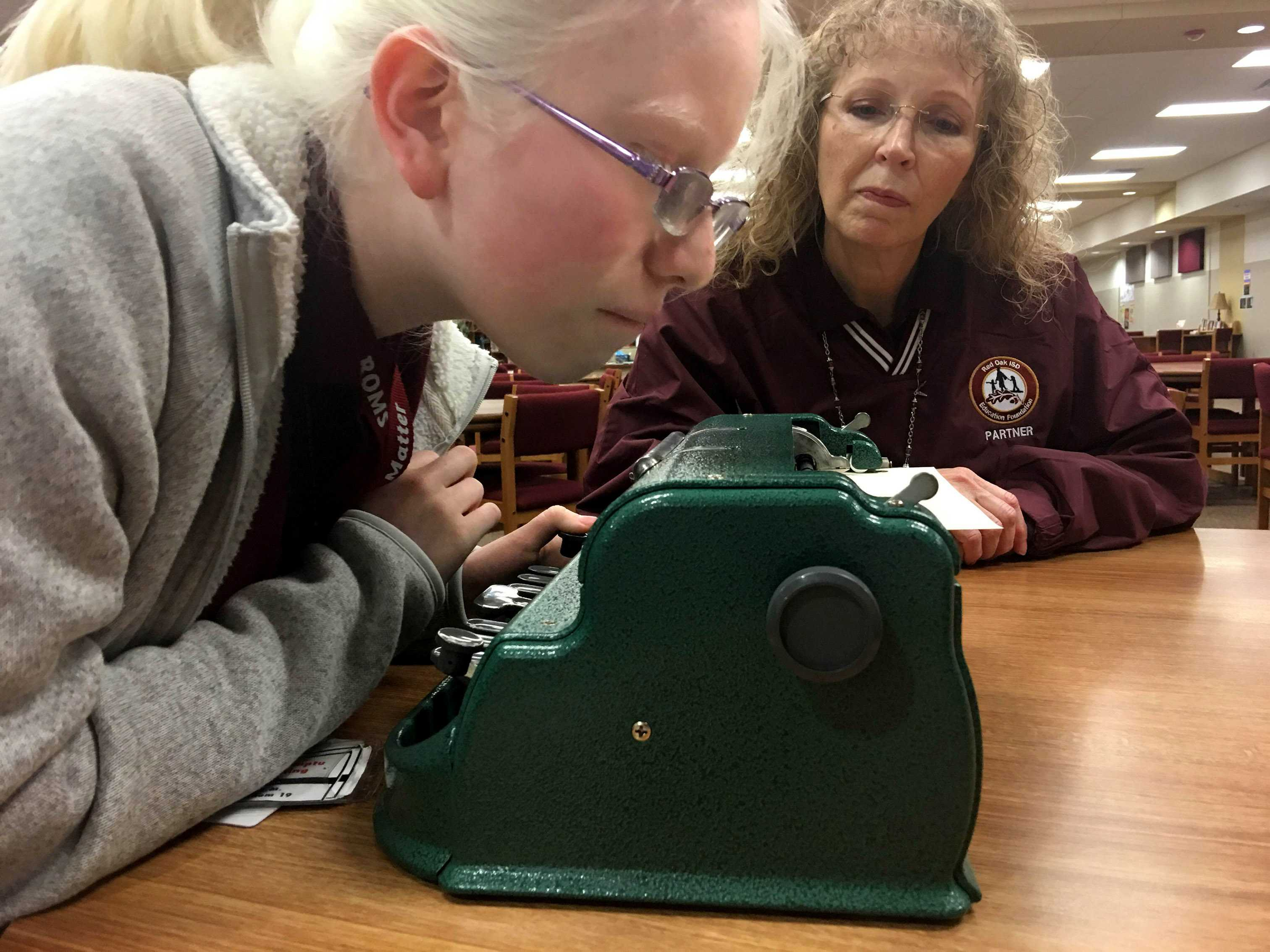 Paulina Diaz, left, practices using a Braille typewriter under the supervision of Terry Layfield, a teacher of the visually impaired, in the Red Oak Middle School Learning Commons on Dec. 16, 2015. Diaz is affected by albinism, which caused her loss of vision. She has been working with Layfield since she was 5 years old, and sends letters written in Braille to another of Layfield's students at Red Oak High School.