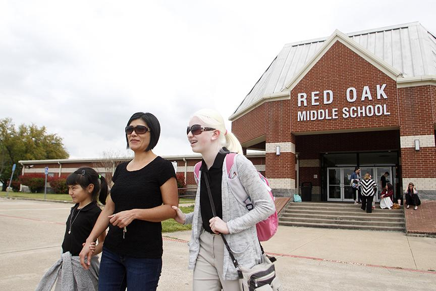 Ilda Diaz, second from left, and her daughters Carolina, left, and Paulina walk to their car after Ilda picks up Paulina from school March 29. Due to her albinism, Paulina must be careful to wear sunscreen and sunglasses when outside during the day.