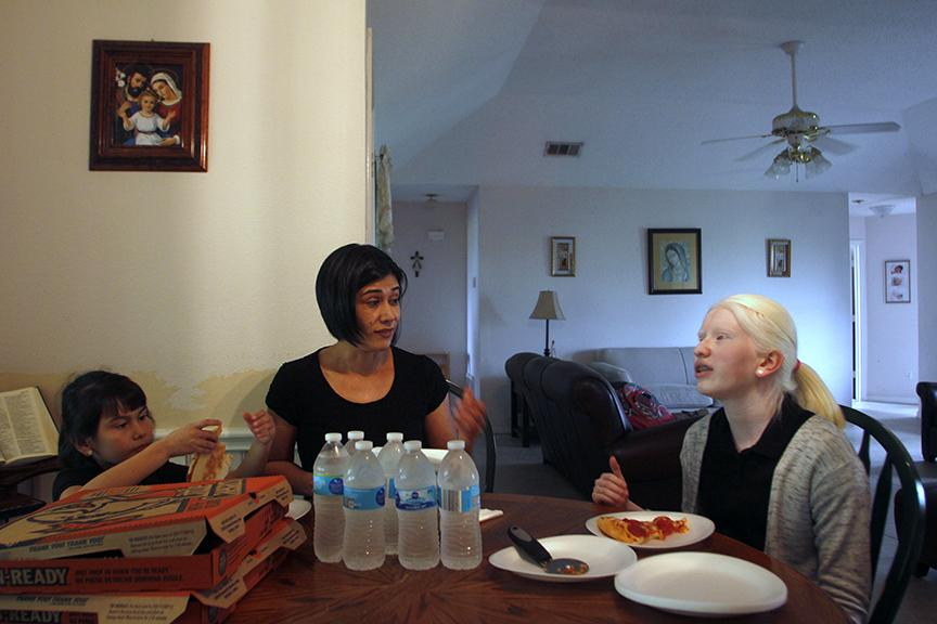 Paulina Diaz, right, talks about her day at school with her mother, Ilda, and her sister, Carolina, during dinner at their home in Palmer on March 29. The three share a close bond; two years ago, they travelled to San Diego together for an albinism conference. Carolina does what I do when I'm not around, she takes care of Paulina, Ilda said. When they're in a different environment, Carolina takes care of Paulina. When they're in a safe, familiar environment, Paulina helps Carolina. Carolina just knows the times when she needs to watch over her.