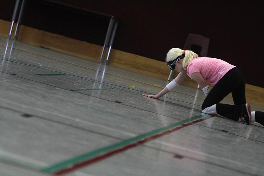 """Paulina Diaz uses her hands to follow a line of tape back to her spot on the goalball court. Goalball is a game designed for the blind and visually impaired, in which they must listen for the ball's jingle as it is propelled toward them and attempt to block it with their bodies. """"It gives us an opportunity to play on a team,"""" said Libby Daugherty, one of Diaz's teammates. """"My dad's philosophy is that whenever we come to practice, the parents are to stay on the bleachers, and we are completely in control of the court. It's our world, and we have to figure it out."""""""