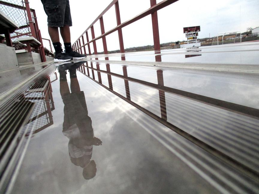 Gray clouds loom over Red Oak ISD's Goodloe Stadium where eighth grader Zorian Burley stands in the bleachers during a shooting assignment for photography class, Monday, March 7, 2016. Showers are likely to continue through Friday night with high temperatures in the mid 60s and lows in the mid to low 50s, according to the National Weather Service. Warm and sunny weather is expected for the start of spring break with highs in the low 80s.