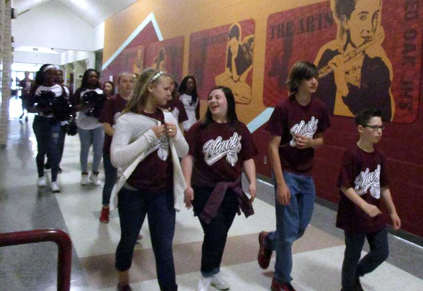 Red Oak Middle School Destination Imagination team members Laney Fleming (from left), Abby Anderson, Connor Nunley and Colton Purdue walk through the halls during a send-off parade as they head to the state tournament in Anna, TX  on April 1.