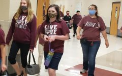 Students and staff wear  protective gear including masks and keeping a safe  distance from each other.